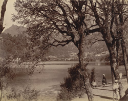 View of Naini Tal Lake, looking towards the north end from the eastern shore. Indian figures are posed amongst trees in the foreground